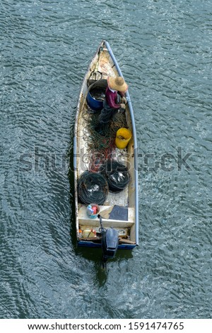 Unidentified Malaysian fisherman takes out caught fish from fish traps in the Johor Strait near Pasir Gudang.