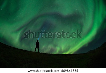 Stock Photo Unidentified man enjoying the Northern Lights (Aurora Borealis) during a Solar Storm. Low light condition.