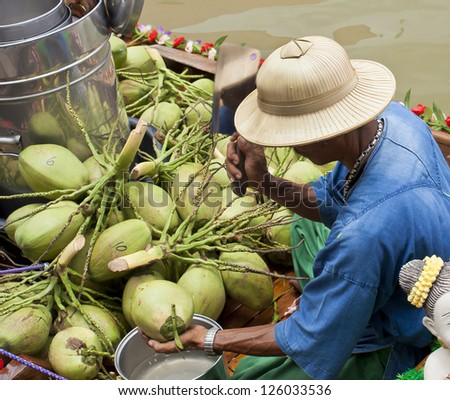 Unidentified man was chopping the young coconut for sale