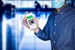 unidentified man wearing a face mask and holding a passport and a Green pass with meaningless QR code representing a certificate of vaccination.Airport on the background.