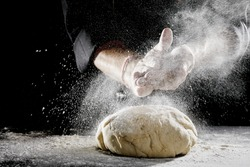 Unidentified man wearing black chef suit hidden in the shadows sprinkling white flour over brightly lit blob of dough