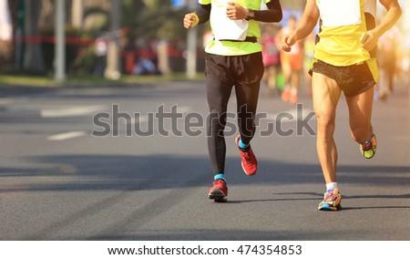 Unidentified marathon athletes legs running on city road #474354853