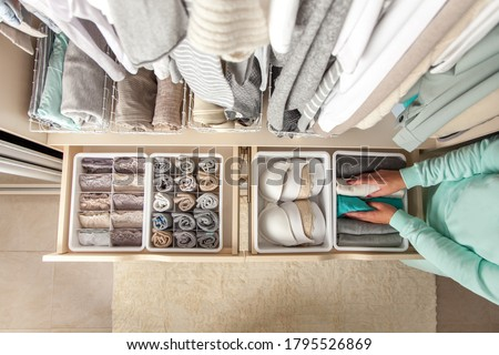 Unidentified neat housewife puts container with socks and pantyhose on wardrobe drawer during general cleaning by modern storage system. Concept of beautiful and comfortable organization Foto stock ©