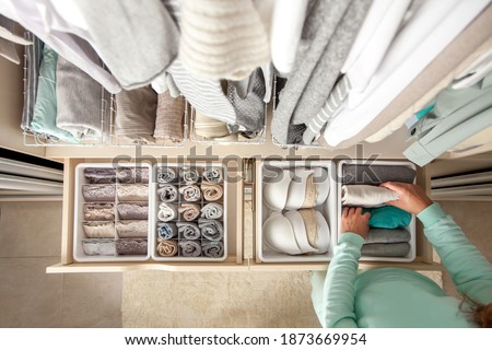 Unidentified neat housewife puts container with socks and pantyhose on wardrobe drawer during general cleaning by modern storage system. Concept of beautiful and comfortable organization