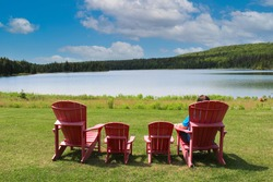 Unidentified person sitting alone on a red plastic chair admiring the view at Wolfe Lake in Fundy National Park in New Brunswick, Canada