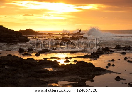 Unidentified photographer in beautiful landscape of rock and sea in sunrise time at Waikawa bay, South Island, New Zealand