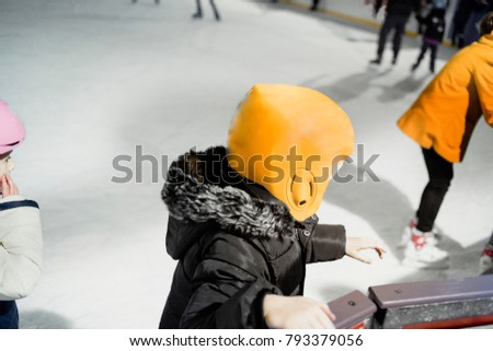 Unidentified rescue extreme kid child  on rink.  Ice Skaters skating on a public child e rink , wearing  yellow  helmet and uniform . Concept of learning    skating.