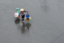 Unidentified street vendor on street in a raining day in Hanoi, Vietnam