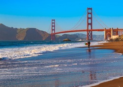 Unidentified surfer at sunset at Baker Beach by the famous Golden Gate Bridge in San Francisco, California, United States of America