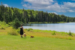 Unidentified woman walking two small dogs at Wolfe Lake in Fundy National Park, New Brunswick, Eastern Canada