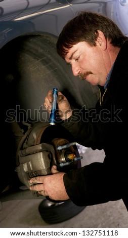 Uniformed Auto Technician Uses Mini Light to check brakes on a Car