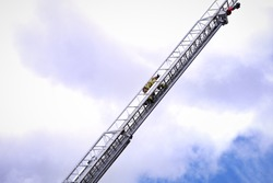 Uniformed firefighter climbing up fire ladder for his mission to save the life during the disaster. Great composition and motion against cloudy blue sky. Copy space.