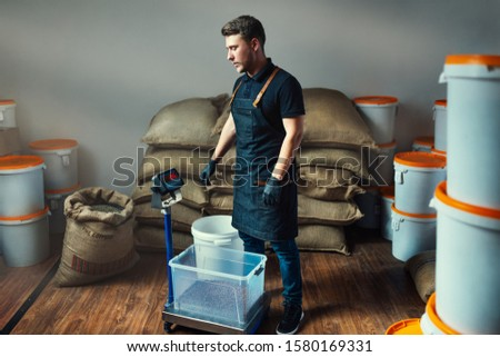 uniformed worker weighs roasted coffee in a transparent tray on a scale in a coffee industry warehouse with bags and white buckets filled with beans