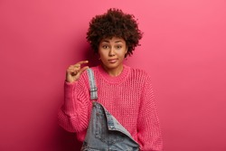 Unimpressed curly woman shapes something little and small, demonstrates small decreased price or salary, wears loose knitted sweater and dungarees, shows tiny measure, gestures not big object
