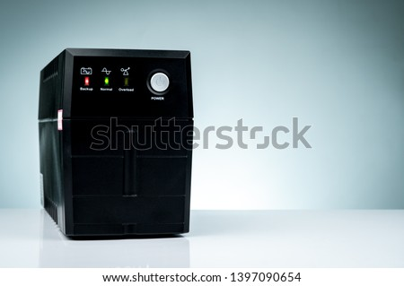 Uninterruptible power supply. Backup Power UPS with battery isolated on table. UPS for PC. Equipment for computer system at office for security. Power protection solutions from home to data center. Сток-фото ©