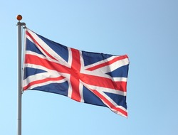 Union Jack flag blowing in the wind on flag pole
