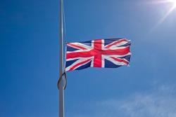 Union Jack flag flying at half mast against blue sky and sun.