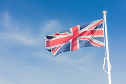 Union Jack Flag Flying From a Flagpole Under a Blue Sky