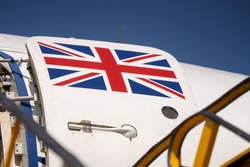 Union Jack flag painted on open door of decommissioned RAF troop transporter aeroplane.  White aircraft with red white and blue flag.