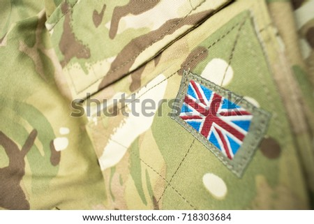 Union Jack / Union flag badge on a British army camouflage uniform. Potential text / writing / copy space around badge. #718303684