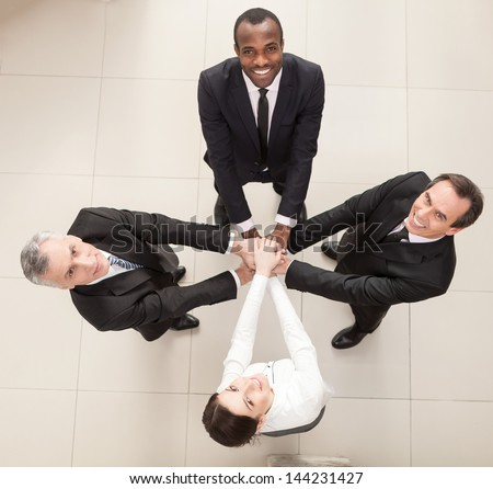 Union of successful businesspeople with hands on top of each other. Top View