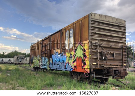 Union Pacific railroad car covered with graffiti on a siding track, hopper cars for grain transport in a background