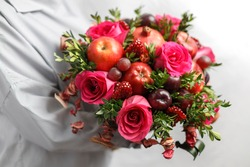 Unique bouquet of pomegranates, red apples, black plums and roses in hands of a woman