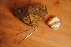 Unique cloth mask with Indonesian Batik pattern on the wooden table with yarn and sewing tools hold by women's hand. art and fashion concept.