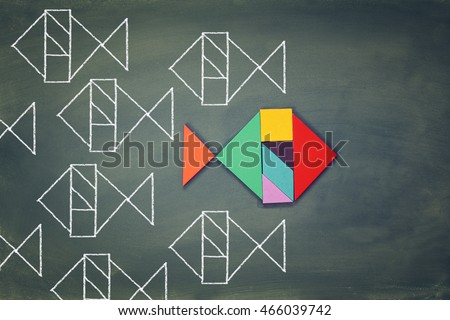 unique different fish made from tangram puzzle shape,swimming opposite way of identical ones. Courage and success concept