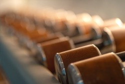 Unique edition. Stylish male dumbbells made of wood and steel lying in a row. Sports equipment, healthy lifestyle, sport. Horizontal shot. Selective focus. Copy space