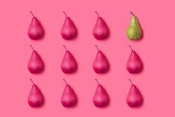 Unique green pear among many pink ones against vibrant pink background. Minimal summer organic fruit geometrical layout. Creative individuality and difference concept. Flat lay, top view.