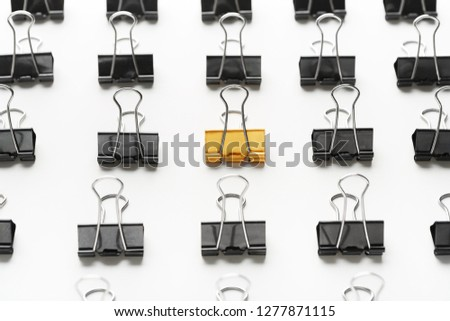 Unique, individuality or think different concept. Golden binder clip standing between black ones on white background