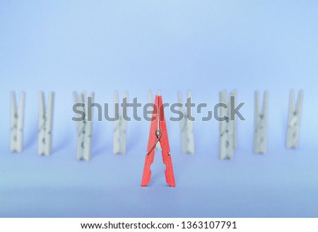 Unique, individuality, outstanding,leadership and think different concept. Red wooden clip stand out of colorless clips on blue backgrounds