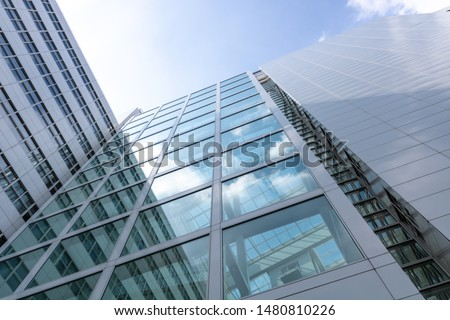 Unique low angle building perspective. bright sun reflecting on the glass of the modern building. shot in the netherlands. #1480810226