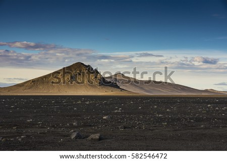 Unique mountain looks like Alien's Planet. A view of brown dried mountain on the black volcanic ashes ground in Landmannalaugar, Iceland.