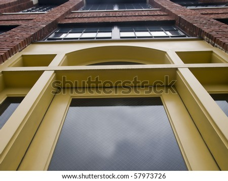Unique perspective of an urban apartment building from the 1920's with beautiful yellow door.