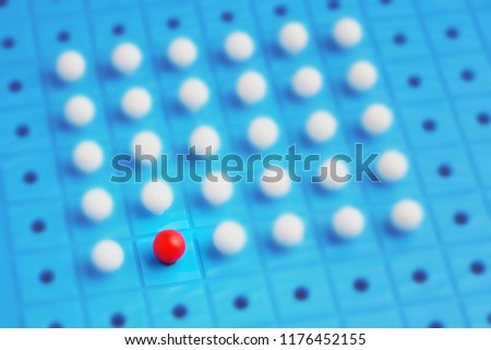 Unique red pin among many white ones. Concept of stand out of crowd, individuality, difference and leadership