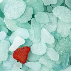 Unique red sea glass isolated on green sea glass background