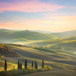 Unique Sundown tuscany landscape in spring time - wave hills, cypresses trees  and beautiful colors of sky. Tuscany, Italy, Europe