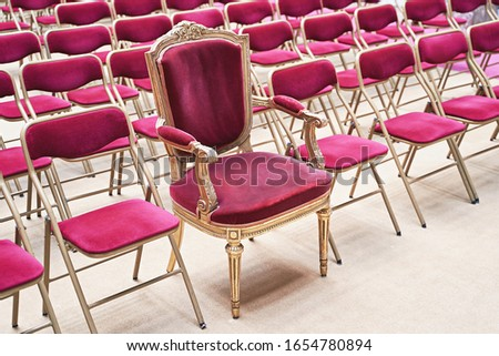 Unique throne or ceremonial armchair with velvet seat and golden details among many simple identical similar chairs. Uniqueness concept. Сток-фото ©