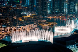 Unique view of Dubai Dancing Fountain show at night. Tourist attraction. Luxury travel destination.