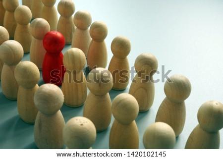 Uniqueness concept. One unique figurine in the crowd.