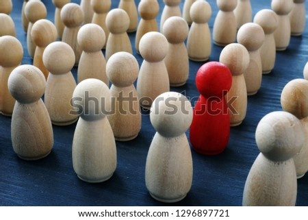 Uniqueness, individuality and difference. Red wooden figure in a crowd.