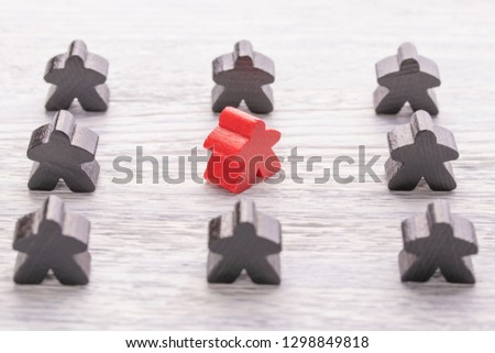 Uniqueness, individuality and difference. Red wooden figure in a crowd of different color on a white wooden table. The concept of disagreement with the majority