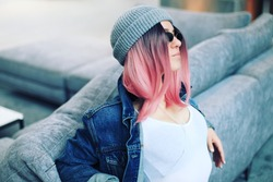 Unisex style, young hipster girl in a vintage denim jacket, gray hat and pink hair listening to music. Non-binary