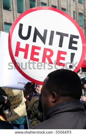 unite here protest with protestors holding stop racism signs and rioting in the streets marching on