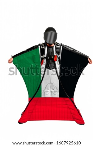 United Arab Emirates trip. Wing men. Extreme men is flying in open air with flag of United Arab Emirates. Skydiver is in free fall.