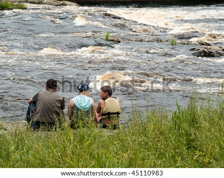 United family - father, mother, son - on river bank