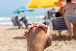 UNITED HANDS OF A MOTHER AND A DAUGHTER ON A BACKGROUND OF A BEACH IN GUARDAMAR DEL SEGURA, SPAIN