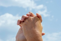 UNITED HANDS OF A MOTHER AND DAUGHTER ON A BLUE SKY BACKGROUND WITH CLOUDS ON A SUMMER MORNING